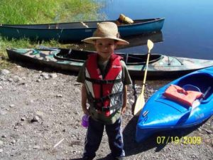 Ready for his first kayak trip with life jacket, sun screen, water bottle, and borrowed hat
